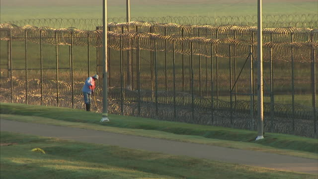 person using hoe on grass between prison fencing drainage ditch next to single lane asphalt path prison incarceration correctional facility the farm... - louisiana video stock e b–roll
