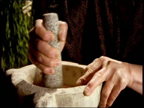 cu,  person using stone mortar and pestle,  close up of hands - macinare video stock e b–roll