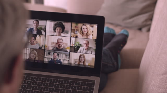 stockvideo's en b-roll-footage met person using video conferencing technology from sofa for video call with colleagues at home and in offices - lockdown