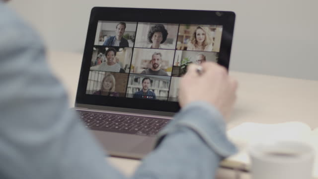 vídeos de stock e filmes b-roll de person using video conferencing technology in kitchen for video call with colleagues at home and in offices - escritório em casa