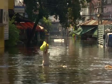 a person wades through flood waters holding a bag - camminare nell'acqua video stock e b–roll