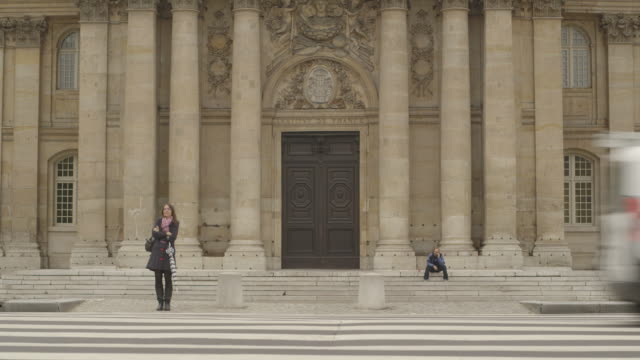 A person waits at a wide zebra crossing outside the Institut de France as traffic passes, Paris.
