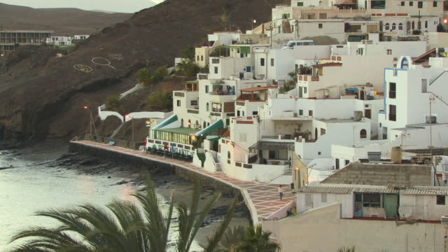 ha, ws, person walking along paved promenade at foot of hillside village / las playitas, fuerteventura, canary islands, spain - unknown gender stock videos & royalty-free footage