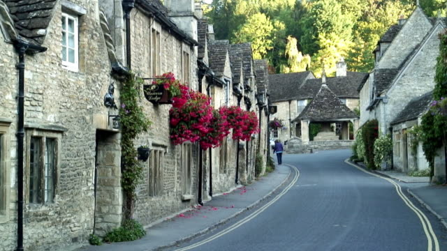 WS Person walking down street in old stone village / Castle Combe, Wiltshire, England