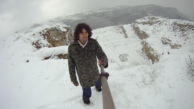 stockvideo's en b-roll-footage met pov van persoon die in een de winterbos loopt. knappe krullende behaarde militaire veteraan van middelbare leeftijd die pret in de sneeuw op een zonnige de winterdag en het vloggen heeft. - sunny