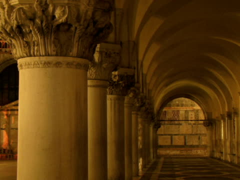 t/l ms person walking past doges palace colonnade at night / venice, italy - palace video stock e b–roll