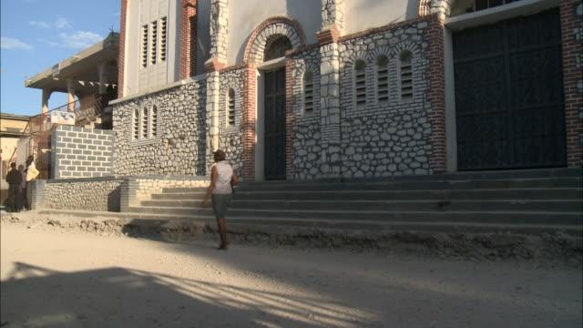 tu person walking past white building / mirebalais haiti - hispaniola stock videos & royalty-free footage