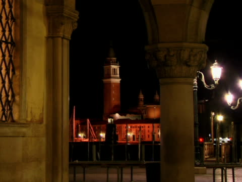 t/l ms person walking through square near doges palace at night with church of san giorgio maggiore in background / venice, italy - unknown gender stock videos and b-roll footage