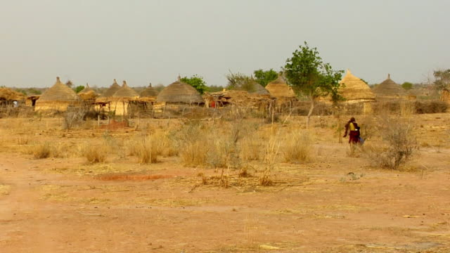 ws, person walking towards village with thatched roof huts, niamey, niger - ニジェール点の映像素材/bロール