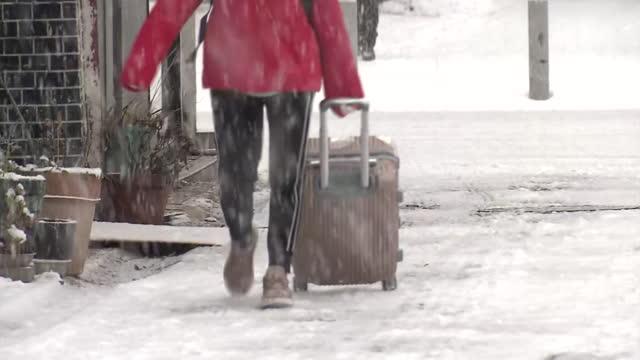 person walking with trolley bag in snowstorm, fukuoka, japan - fukuoka prefecture stock videos & royalty-free footage