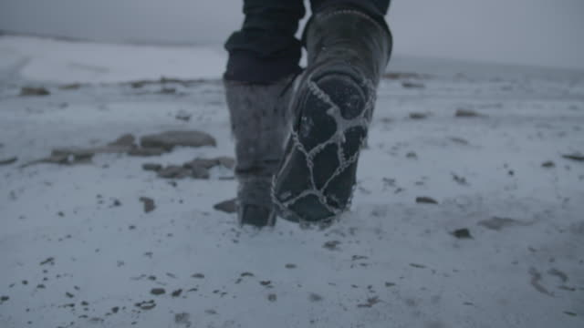 person walks in snow boots, slow motion close-up - walking stock videos & royalty-free footage