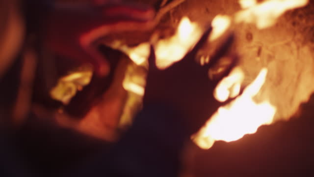 Person warms hands by campfire, close up