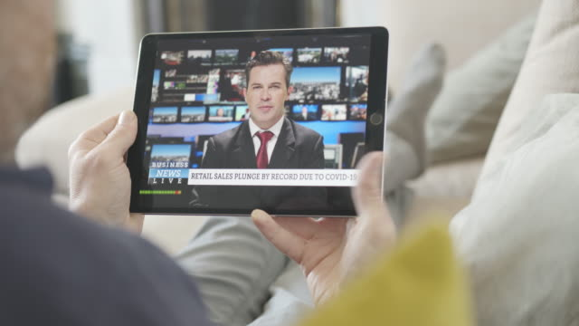vidéos et rushes de person watching live stream news broadcast from sofa with business news during the great lock down economic crisis, newscaster, wireless technology, digital tablet - media
