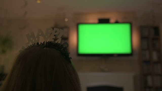 person watching tv puts on happy new year headband - solitude stock videos & royalty-free footage