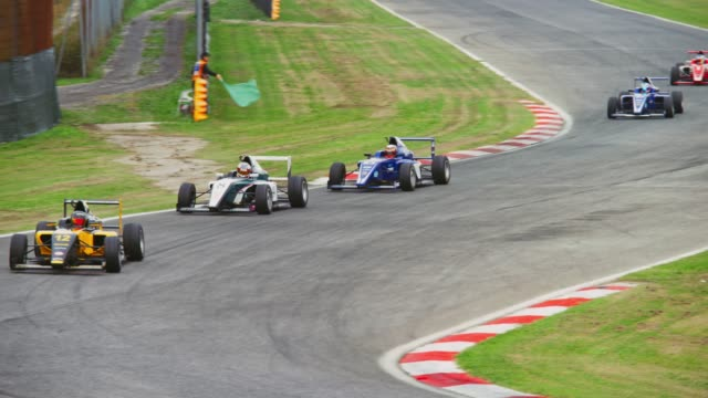 person waving green flag as the formula cars race around the turn - contestant stock videos & royalty-free footage