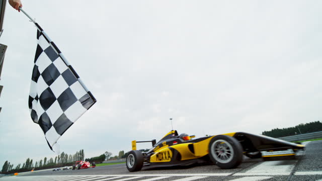 slo mo ld person waving the checkered flag in the race as the formula drivers drive across the finish line - winning stock videos & royalty-free footage
