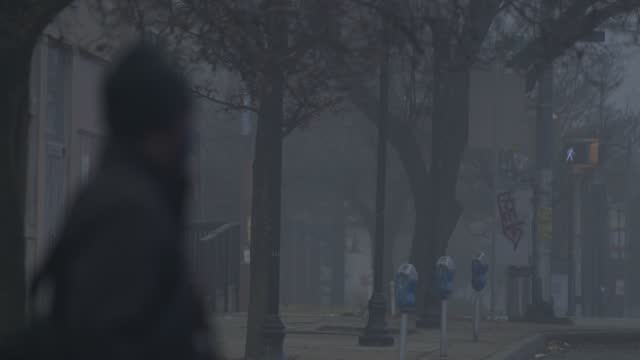 person wearing a mask on north avenue emerges from a thick layer of fog during the coronavirus pandemic on december 12, 2020 in baltimore, maryland.... - focus on background stock videos & royalty-free footage