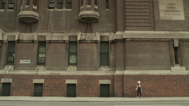 A person wearing a white sun hat walks along the pavement of Lexington Avenue in Manhattan next to the 69th Regiment Armory, New York City, USA.