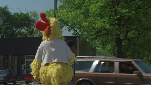 ms, person wearing chicken costume serving food sample on street, dropping tray and leaving  - stillstehen stock-videos und b-roll-filmmaterial
