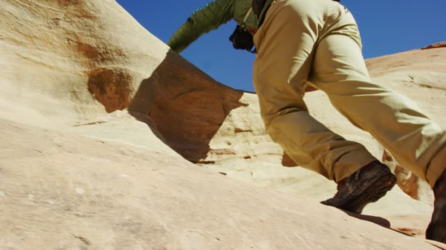 a person wearing hiking gear and boots climbs up a rock formation under a clear, blue sky - boot stock videos & royalty-free footage