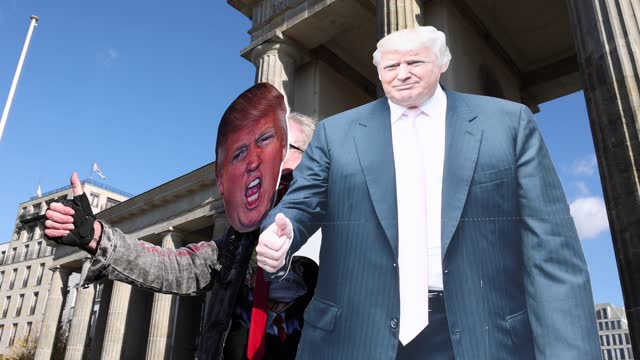 person wearing mask with the image of us president donald trump gestures near supporters of democrats abroad rally in front of the brandenburg gate... - berlin stock videos & royalty-free footage