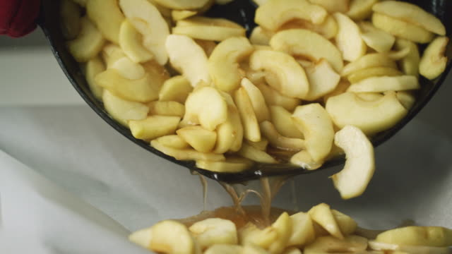 a person wearing oven mitts pours cooked sliced apples and their juices from a cast iron skillet on to a baking sheet covered in parchment paper - cibo cotto video stock e b–roll