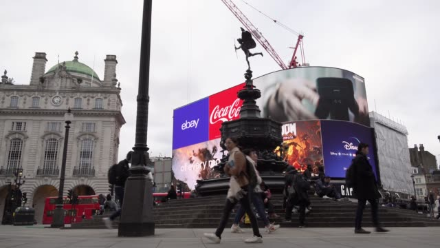 a person wearing surgical face mask walks in front of the neon advertisement billboard sign at piccadilly circus on the day after prime minister... - commercial sign stock videos & royalty-free footage
