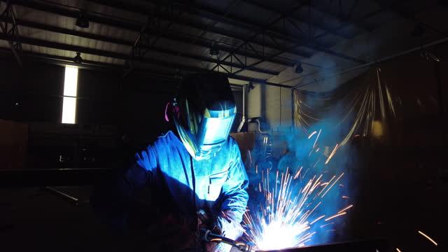 person welding in protective gear and helmet in the dark - welding helmet stock videos & royalty-free footage