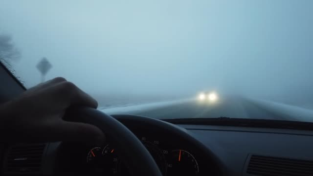 a person with a hand on the steering wheel drives a car on a snowy, foggy road in the county in winter - headlight stock videos & royalty-free footage