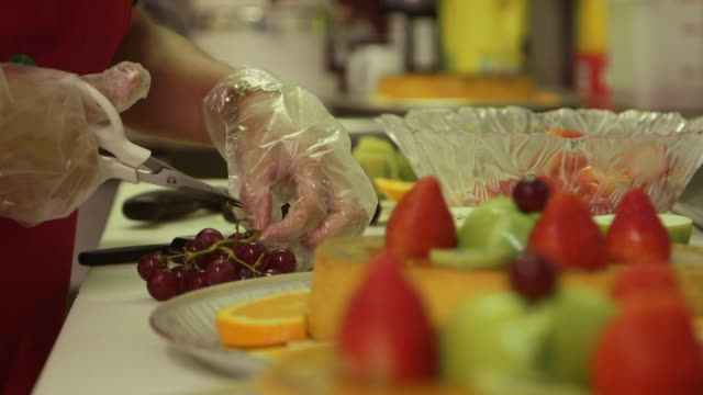 Person with gloves cuts grapes flan preparation