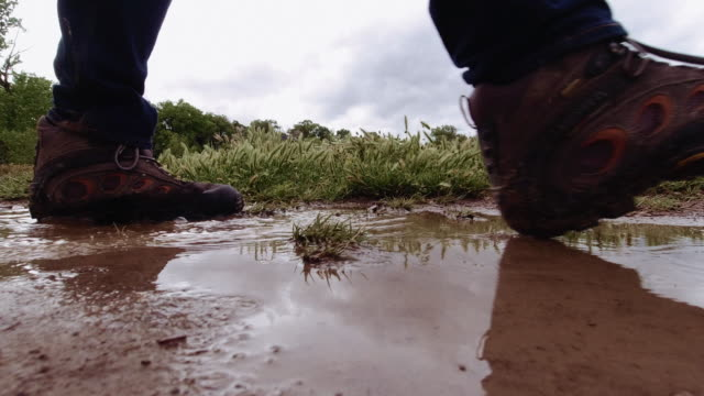 vídeos de stock e filmes b-roll de a person with hiking boots and jeans walks through a muddy puddle of water in an uncultivated area under a stormy sky - passos