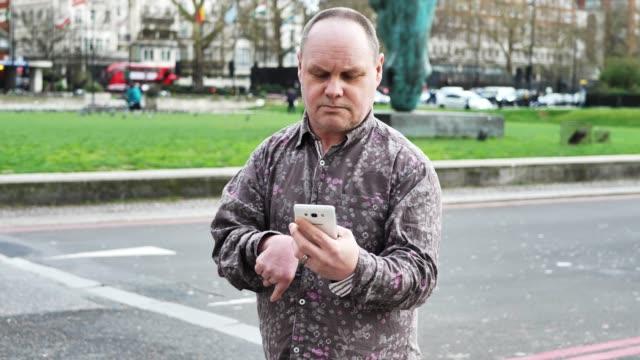 person med fysiska funktions nedsättningar som har problem med att använda mobil telefon - 45 49 år bildbanksvideor och videomaterial från bakom kulisserna
