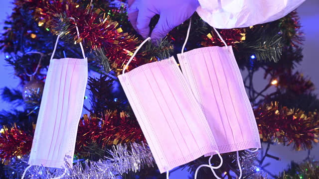 a person with protective gloves is decorating the christmas tree with pink protective masks (change the christmas balls for the masks). - safety stock-videos und b-roll-filmmaterial