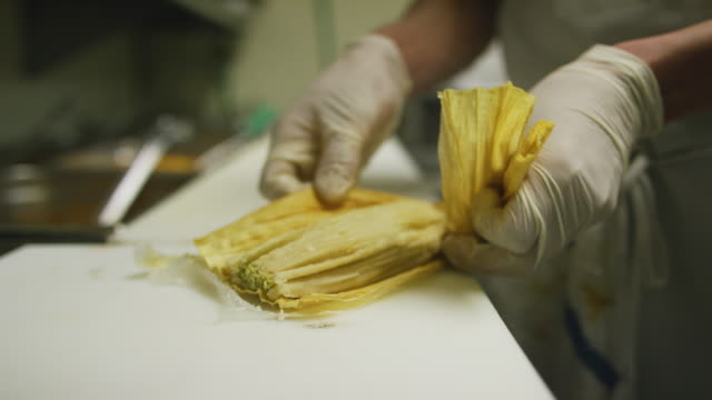 a person with rubber gloves unwraps a steaming hot tamale in a commercial kitchen in a mexican restaurant - mexican restaurant stock videos & royalty-free footage