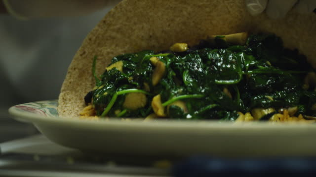 a person with rubber gloves wraps a burrito with spinach, mushrooms, and rice on a plate in a mexican restaurant - mexican restaurant stock videos & royalty-free footage