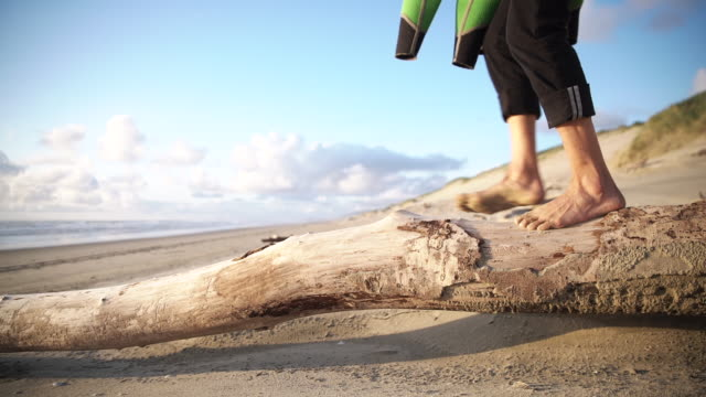 Person with surfboard walks on beach log