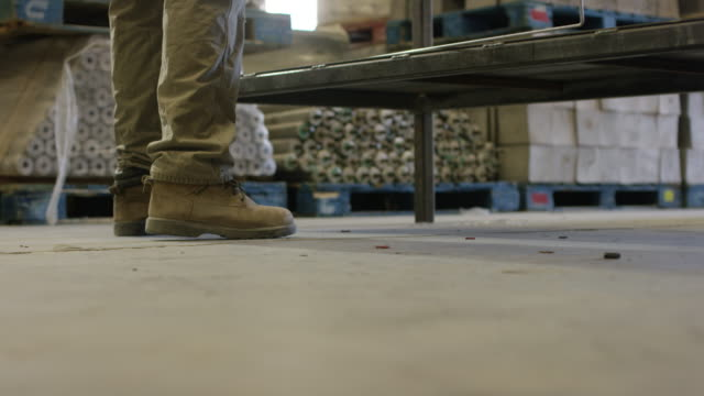 タン作業ブーツと製造施設の作業ベンチまでカーキ色ズボン ステップ人 - 製造業関係の職業点の映像素材/bロール