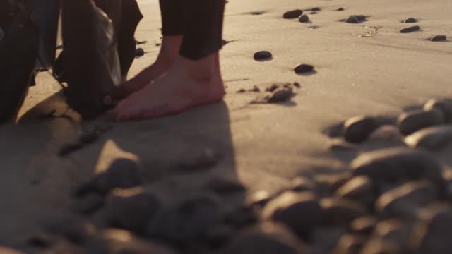 vídeos de stock, filmes e b-roll de person with wetsuit on sandy beach, close up - diving suit
