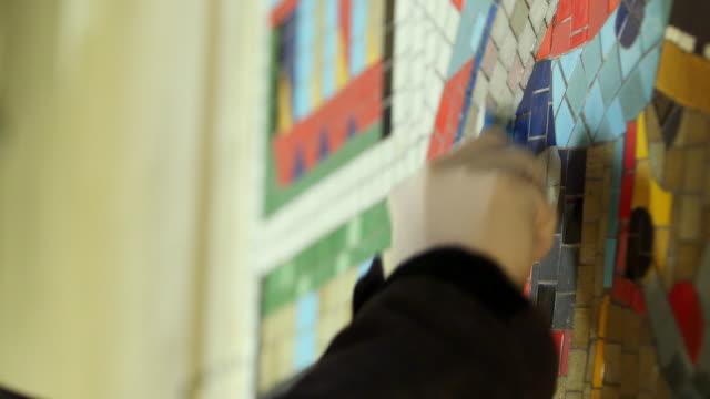 CU TD Person working on mosaic renovation at Tottenham Court Road Underground Station / London, England, United Kingdom