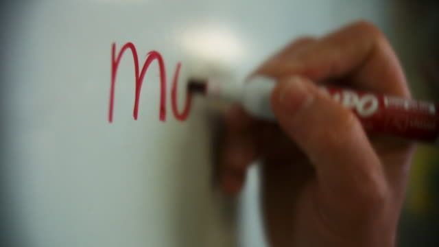 vídeos de stock e filmes b-roll de a person writes the word money on a whiteboard. - pilot