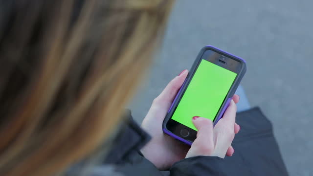 Person Young lonely woman surfing on smart phone green screen