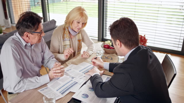 Personal banker explaining options to his clients at a meeting in their home