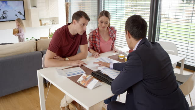 Personal banker explaining options to young couple in their home
