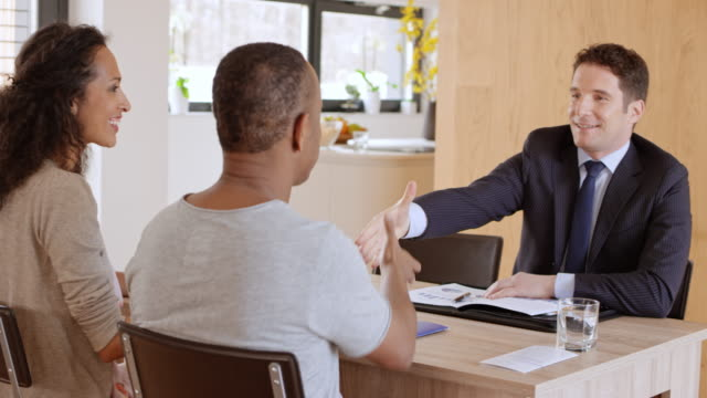 personal banker shaking hands with his clients on a meeting in their home - brochure stock videos & royalty-free footage