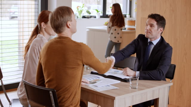 Personal banker visiting a young couple and shaking hands when the meeting ends