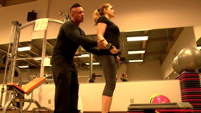 stockvideo's en b-roll-footage met personal fitness trainer & client working out - haar naar achteren