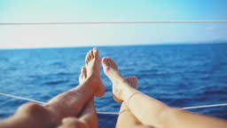 4K Personal perspective barefoot couple relaxing on sunny sailboat on sunny ocean, real time