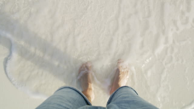 ms personal perspective barefoot man standing in ocean surf on white sand beach - gopro stock videos & royalty-free footage