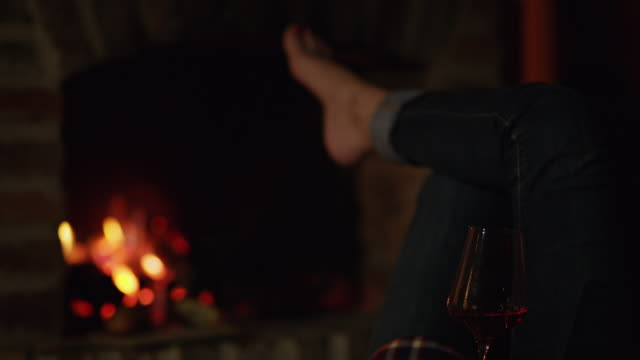 4k personal perspective barefoot woman relaxing with red wine by cozy fireplace, real time - barefoot stock videos & royalty-free footage