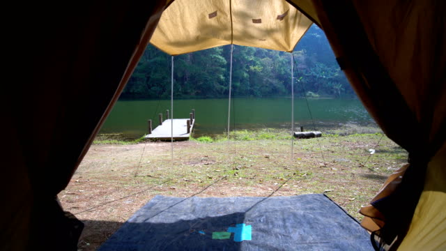 personal perspective looking through tent to lake view. - tenda da campeggio video stock e b–roll